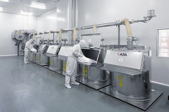 Manufacturing employees dumping bag at AZO Feeding Hopper